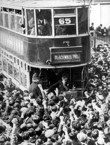 Workers pass an overturned tram during in Hackney, NE London, during the 1926 British General Strike.  In general, goods travelled through Britain with authorisation from the workers or under police and troop protection.