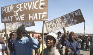 Protesters hold placards during a peaceful protest march in the Ramaphosa squatter settlement