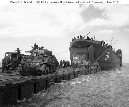 Sherman tanks landing from transporting ship on to pier assembled at Normandy beach.  The sections were towed across the sea from Britain by tugboats then assembled under fire.