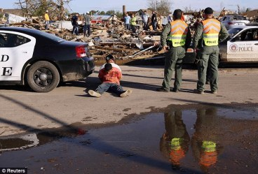 Alleged looters sit handcuffed under police guard in Oklahoma after storm May 2013.  Nearby, neighbours whose homes were destroyed and who accused the men of looting.