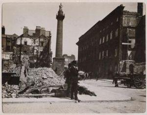 """Destrucción por bombardeo británico en el 1916 a la calle Henry y la esquina del Moore Street. La columna es la de Nelson (ahora reemplazado por el """"Spire"""") en la calle O'Connell. La ruina del GPO está a la derecha, cerca a la columna."""