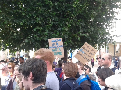 Two placards in the crowd earlier, a reminder of what it was about