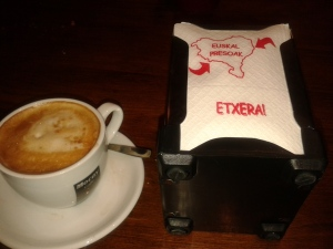Cafesnea (coffee and milk) with the standard Herriko tissues, stamped with the slogan calling for the Basque prisoners to be sent home from dispersal (and also to be freed).