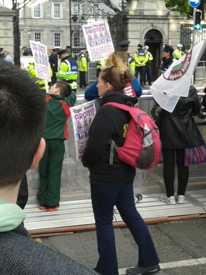 Among others, schoolchildren lean on the barrier which facing the Dáil, the Irish Parlia