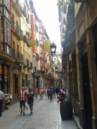 Street in the Casco Viejo medieval part of Bilbao, showing decorations for the Bilbo festival in August