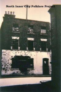 "The bullet-pocked ""white house"" in Henry Place, facing up Moore Lane"