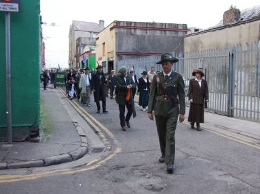 Volunteer attaching Tricolour to rifle as near the GPO, walking through Henry Place (Photo: Bart Hoppenbrouwers)