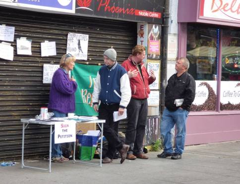 Moore Stret December 2014, the weekly campaign stall in its early days -- Brónagh Ní Loing, Diarmuid Breatnach at table with Mel Mac Giobúin talking to an interested passer-by