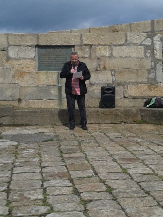 John Crawley giving his oration with the plaque commemorating the landing of the Howth guns behind him