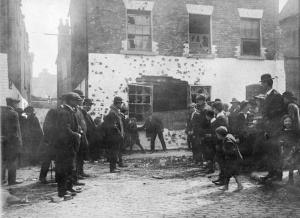 """The `""""white house`"""" in Henry Street, facing Moore Lane, showing the British Army machine-gun and rifle bullet damage from Parnell Street and from the Rotunda tower. The GPO Garrison had to cross this opening to proceed onwards to Moore St (to the right)."""